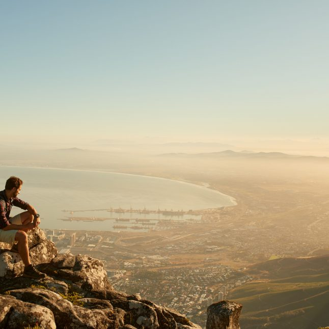 Shot of a young hiker admiring the view from the top of the mountain