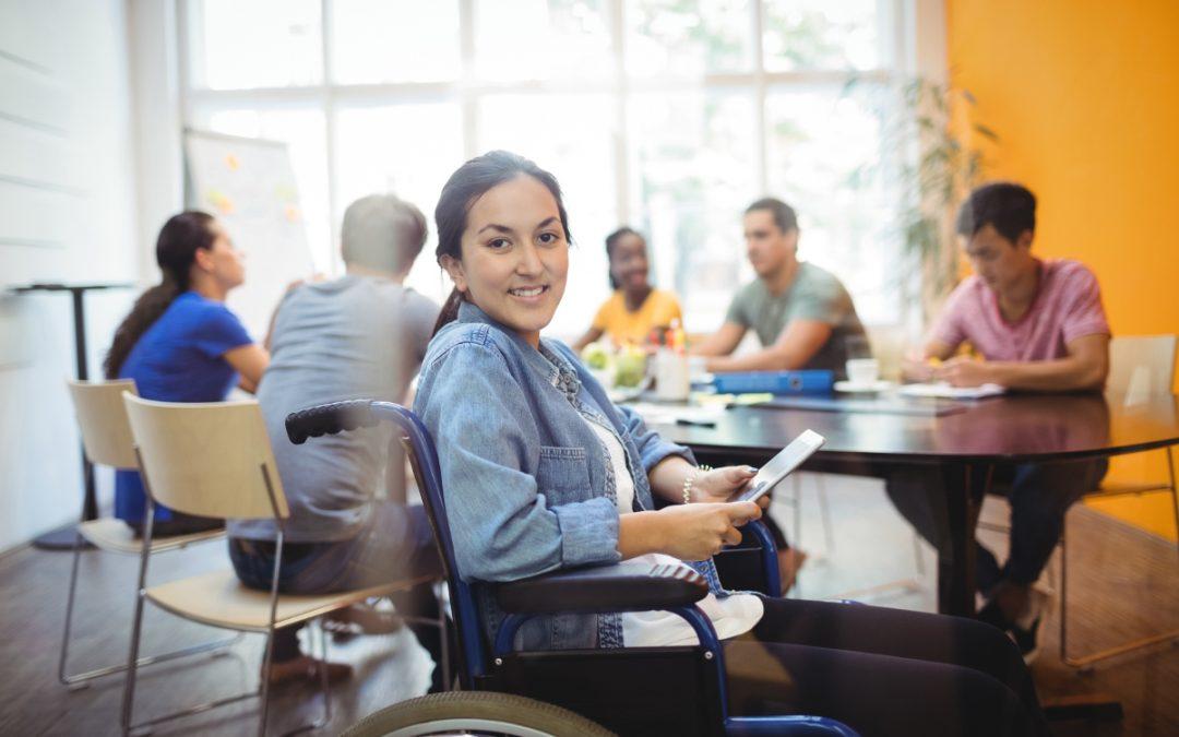 Imágen de una mujer en silla de ruedas trabajando con un grupo de personas en una oficina